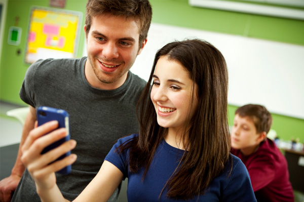 teen on smartphone in classroom