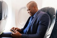 man-on-plane-using-smartphone