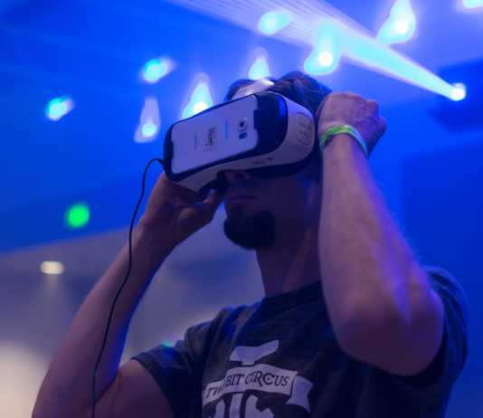 Guy tries virtual glasses headset during VRLA Expo, virtual reality exposition, event at the Los Angeles Convention Center in Los Angeles.
