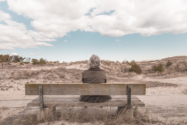 elderly person sitting on a bench near a lot of sand dunes