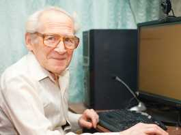 smiling happy old man sitting near computer and holding mouse